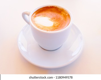Small beverage drink of strong coffee made with milk in a white ceramic cup with saucer