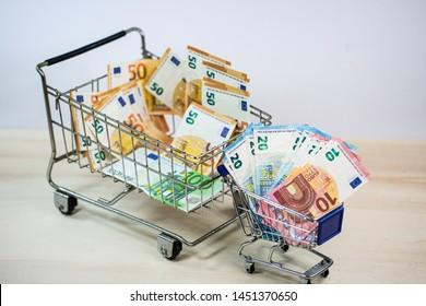small and big shopping cart full of money, symbolic