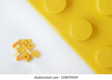 Small and big yellow plastic constructor bricks on white background. Popular toys.