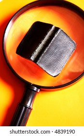 Small black book lying on a big magnifying glass on a yellow and orange background