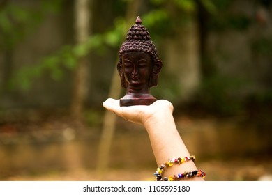 Small black bust of Buddha on a white female palm
