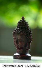 Small black bust idol of Lord Buddha on a beautiful background