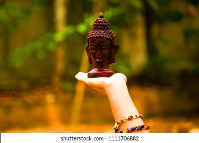 Small, black bust sculpture of Buddha sits on a white female palm