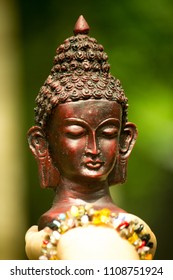Small, black bust sculpture of Lord Buddha on hand