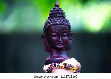 Small black bust sculpture/idol of Buddha on hand