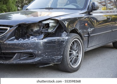 Small black car with damaged headlamp after collision