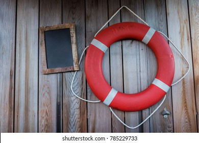 Small black chalk board with lifeguard round float in wooden wall
