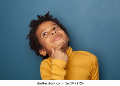 Small black child boy thinking and looking up on blue background