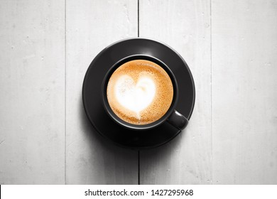 Small black cup of cappuccino coffee stands on white wooden table, top view