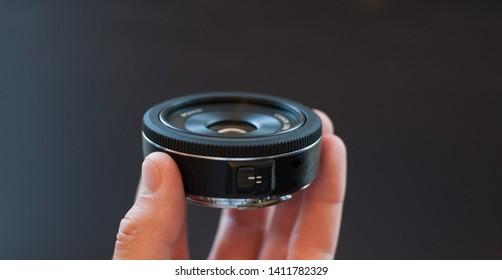 Small black pancake photographic lens.