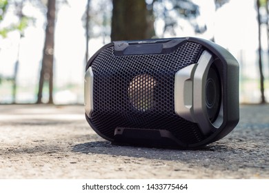 Small black portable speaker placed on the ground in nature – Wireless device for audio playback and listening music