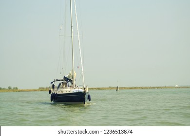 a small black yacht with a mast stands on the sea where people relax, the theme of rest and travel