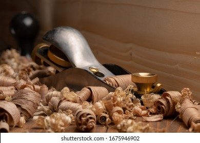 Small block plane with wood shavings. Carpenter cabinet maker hand tools on the workbench.