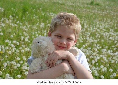 Small blond boy on meadow with puff's flowers, holds white teddy bear firmly in the arm and looks forwards