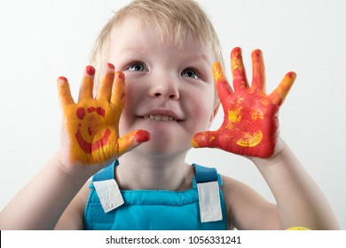 Small blond boy shows his hands dirty with paint in home room, indoors. Child having fun and celebrating holiday with Easter toy bunny
