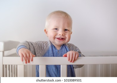 A small, blond short haircut  boy 1.5 years old with blue eyes and sly smile emotions on the face.