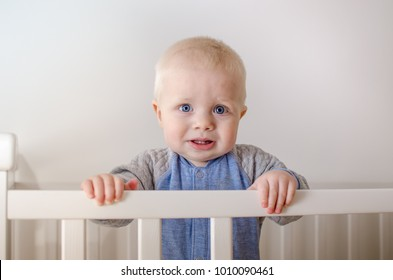 A small, blond short haircut  boy 1.5 years old with blue eyes and scared surprised emotions on the face.