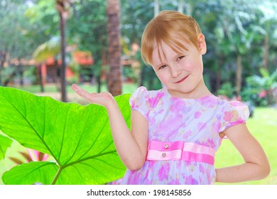 Small blonde girl holding something in his hands on a tropical background