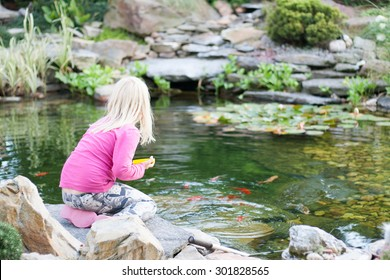 small blonde girl in pink clothes feeding fishes in a garden pond