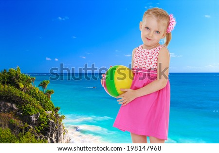 f8709ef6b2 Small blonde girl standing with the ball in his hands against the blue of  the sea
