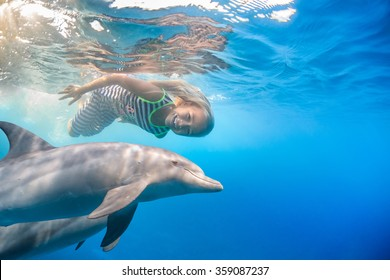 A small blonde seven year old girl swimming with funny dolphins underwater. An ocean life sports extreme design. Kid with marine animal. Red sea diving in blue water.