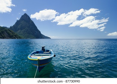 A small blue boat on a beach in St Lucia with Petit Piton in the background