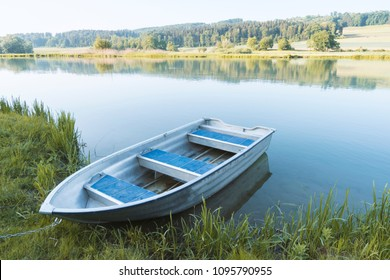 Small blue fisher rowing boat at lake side in the green grass