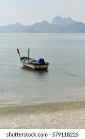 Small blue fishing boat moored at the beach,Sea wave in front with mountains in the background