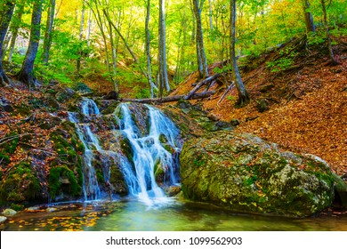small blue waterfall on a mountain river at the autumn