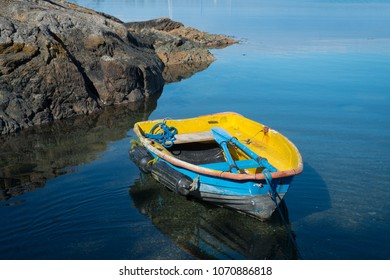 Small blue and yellow fishing boat on tranquil water