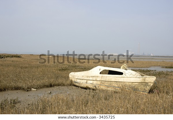 A small boat abandoned  in the mud of a river estuary.