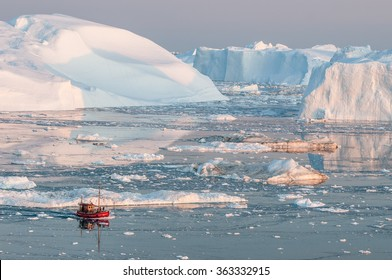 A small boat among icebergs in Greenland