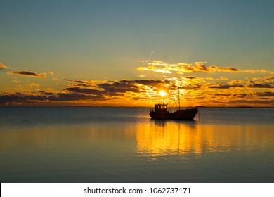 Small boat in Baltic sea in sunset near Saaremaa, Estonia