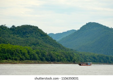 A small boat cruising down the Mekong. Lush mountains are in the background. These dwarf the boat. The sky is blue with white clouds.