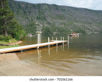 A small boat dock in Grand Lake in Colorado.  The Rocky Mountains are in the background.  The photo was taken in summer.