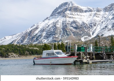 Small boat docked in Waterton Lakes National Park, In Alberta Canada with the Rocky Mountains in the background
