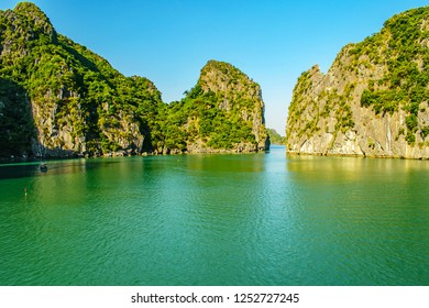 A small boat dwarfed by the tall karsts sails in a natural bay among the karst in Halonh Bat Vietnam November 2018