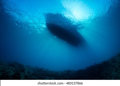 A small boat floats in clear blue water and is silhouetted by bright sunlight in Fiji. This part of the world is known for its coral reefs, warm climate, and beautiful, tropical scenery.