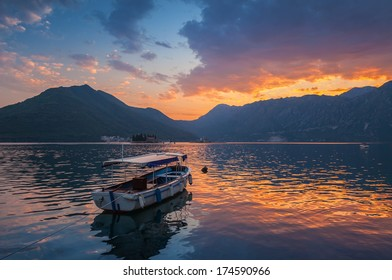Small boat floats moored in Kotor Bay at dusk, Montenegro