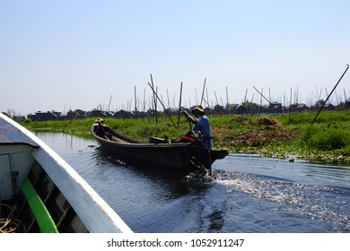 Small boat moves along canals and floating gardens  Inle Lake,  Myanmar (Burma)