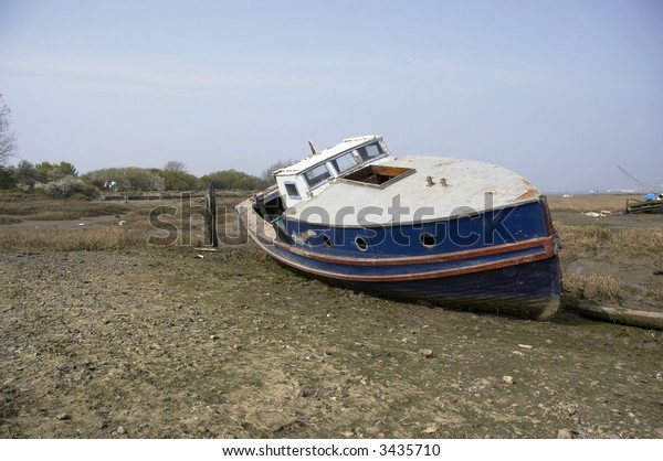 A small boat in the mud of a river estuary