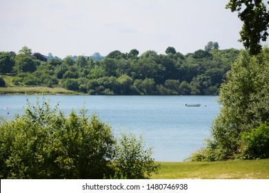 Small boat on Bewl Water reservoir in Tunbridge Wells, Kent. Verdant trees and bushes grow at the water's edge.