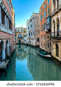 Small boat on a small canal street in Venice of beautiful colorful houses, Italy