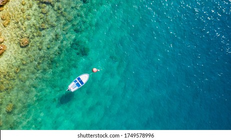 Small boat on turquoise sea water near a rocky shoreline, view from above.