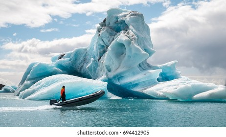 Small boat passes in front of iceberg