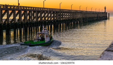 small boat sailing in the harbor of Blankenberge, Belgium, view on the pier and lighthouse at sunset