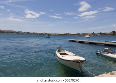 Small boat is tied to the shore, island Krapanj is in background. Dalmatia coast, Croatia.