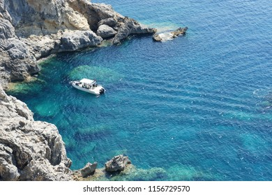Small boat in turquoise clear water of small bay in rocks. Corfu, Greece