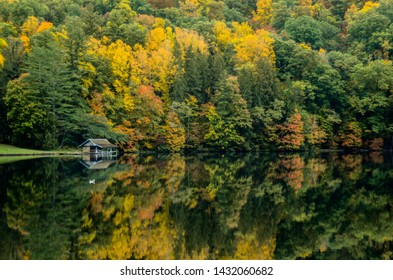 A small boathouse sits along the edge of a lake reflecting leaves changing in autumn