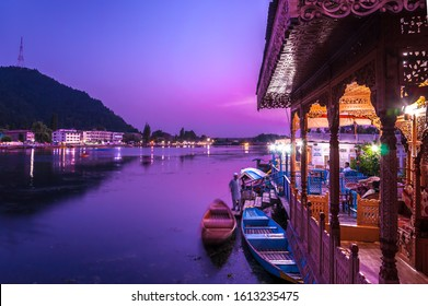 Small boats called Shikara are parked besides colourfully lighted houseboats at dusk in the dal lake in shrinagar, kashmir in India